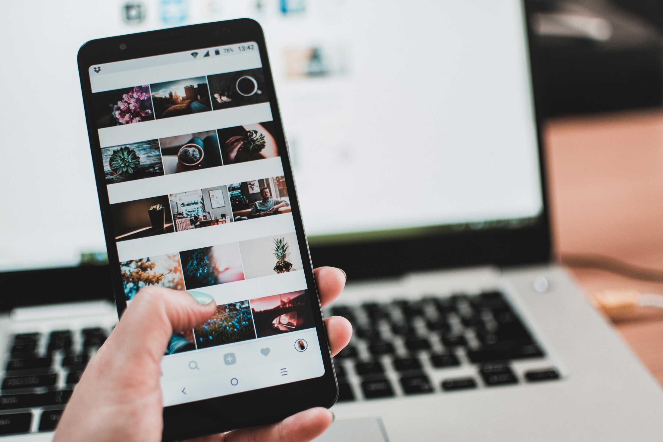 Smartphone in der Hand mit geöffneter App vor einem Laptop
